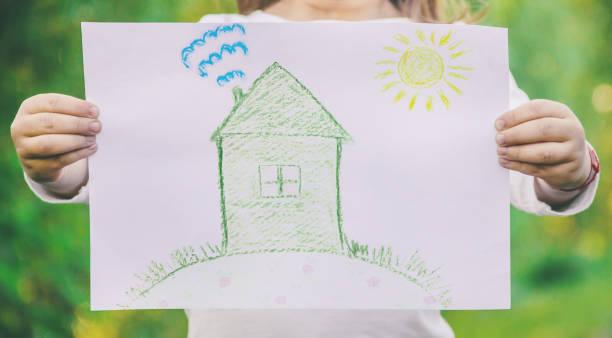 dibujo de una casa verde en las manos de un niño. - dibujar fotografías e imágenes de stock