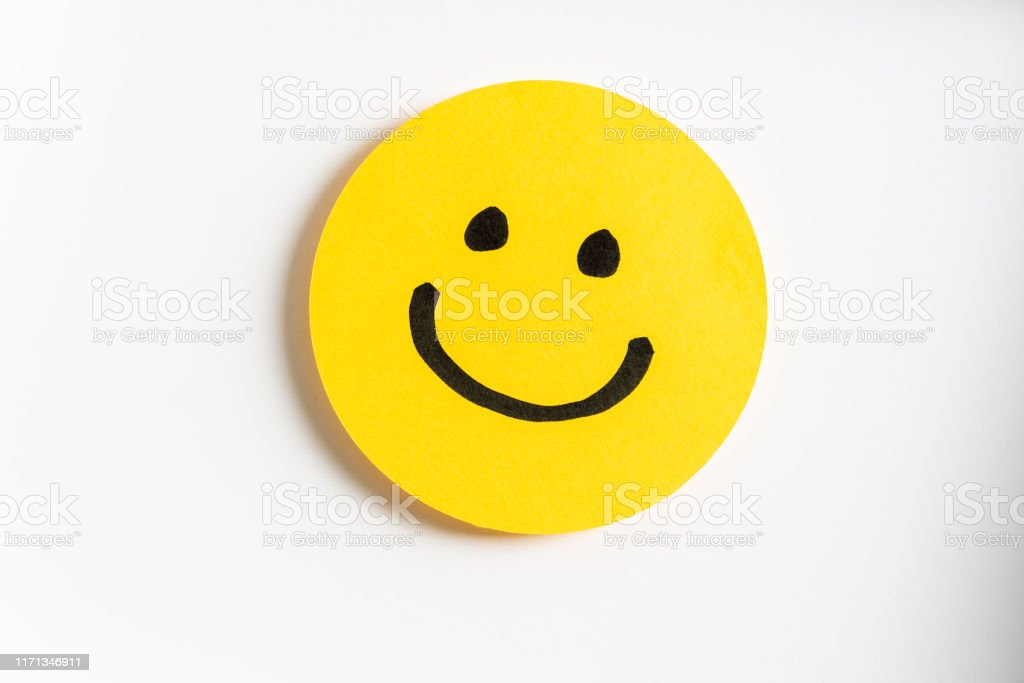 Drawing of a happy smiling emoticon on a yellow paper and white background. Drawing of a happy smiling emoticon on a yellow paper and white background. Anthropomorphic Smiley Face Stock Photo
