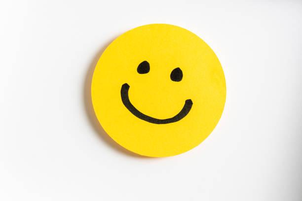 在黃色紙張和白色背景上繪製一個快樂的微笑表情。 - 幸福 個照片及圖片檔
