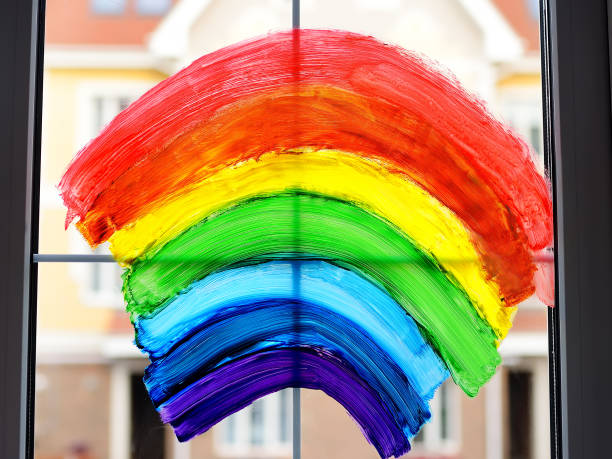 Drawing of rainbow on home window while coronavirus quarantine. Sign rainbow is symbol of hope, means that everything will be OK. Stay in isolation for lockdown of coronavirus. stock photo