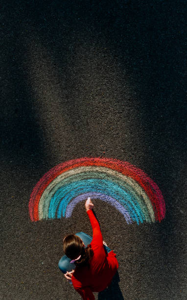 Drawing of Rainbow on the sidewalk during COVID-19 stock photo