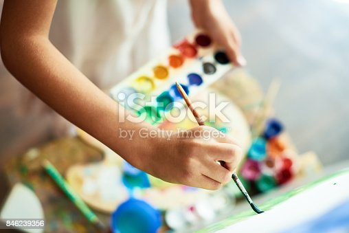Close-up shot of highly gifted little artist drawing with watercolors on canvas, blurred background