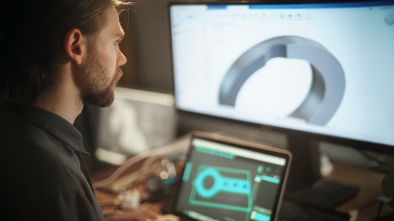 Close up stock photo of a long haired, bearded young man working at a wide computer screen. He's working on software designing a circular component.