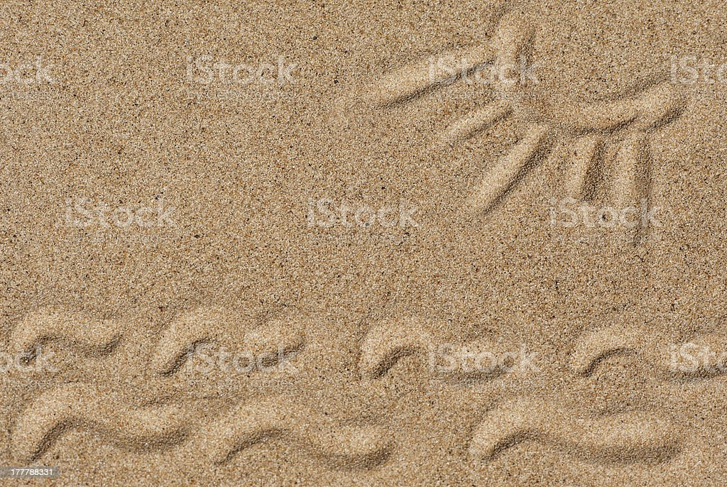 Drawing sun and waves on the sand royalty-free stock photo