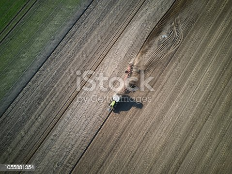 drone view on tractor with harrow on field in autumn sun