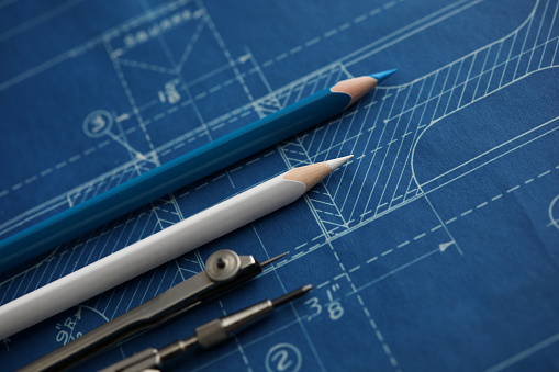 Drawing tools lying over blueprint paper close-up