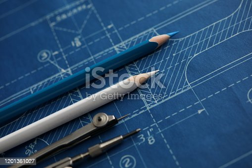 istock Drawing tools lying over blueprint paper 1201361027