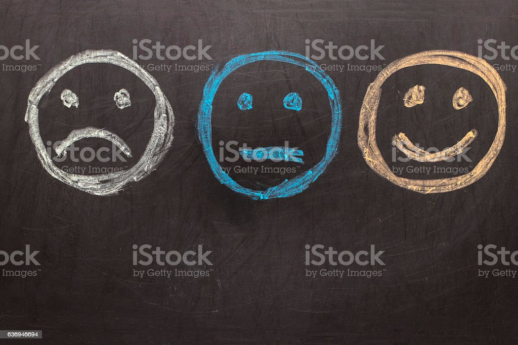 Drawing Unhappy and Happy Smileys on Blackboard stock photo