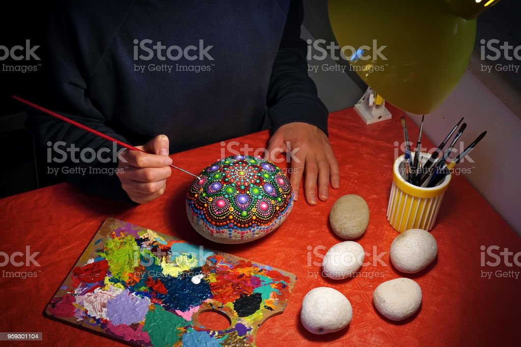 Drawing with a brush a mandala on a stone stock photo