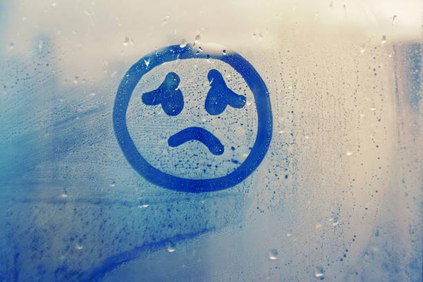 霧のガラス窓の雨滴青い色のコンセプト写真に描かれた悲しい顔 - 憂い ストックフォトと画像