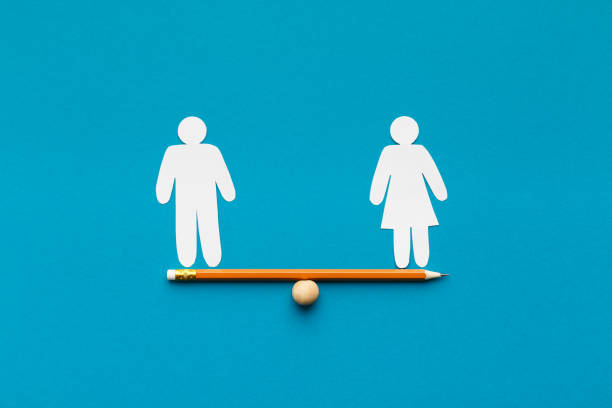 Drawn scales with words man and woman Gender equality in corporate world. Figures of man and woman on pencil seesaw, blue background, copy space human rights stock pictures, royalty-free photos & images