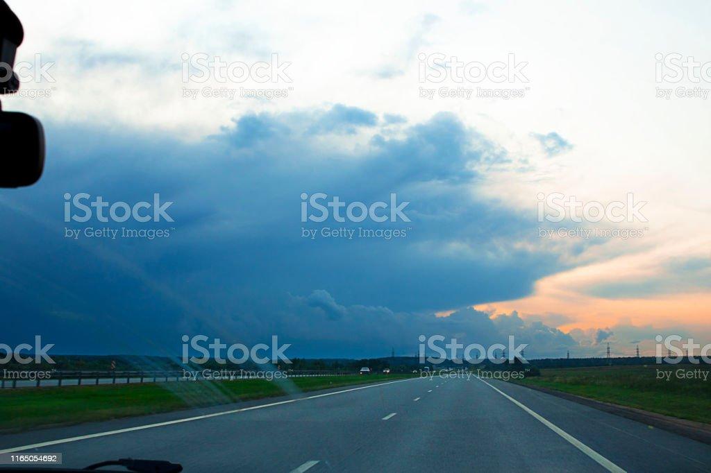 Drive car before rain on asphalt empty grey road. Dark clouds and...