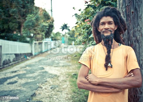 smiling rastaman posing in the street.