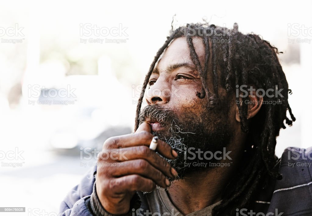 Dreadlocked man daydreams as he smokes a cigarette stock photo