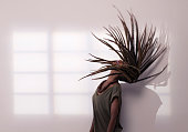 Excited stylish african woman throwing dreadlocks head back to form a hair arc, standing against wall with window shadow.