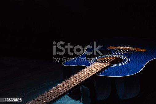 Dreadnought acoustic guitar on a blue wooden background in the dark. Copy space