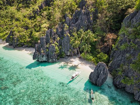 Dream Beach on Entalula Island - El Nido. Hidden Entalula Beach Bay - Lagoon with typical filipino Bangka Tourboat anchored close to the sandy dream beach. Aerial Drone Point of View. Entalula Beach, Bacuit Bay, Mimaropa, El Nido, Palawan, Philippines, Southeast Asia, Asia