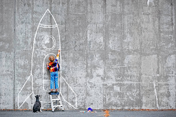 Dream Big Little boy drawing a huge rocket on the wall. dreamlike stock pictures, royalty-free photos & images