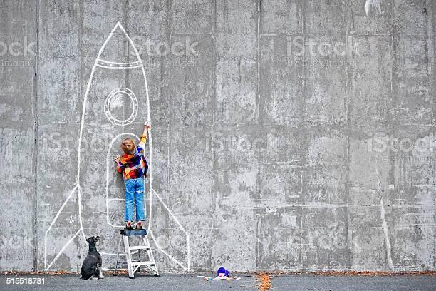 Little boy drawing a huge rocket on the wall.