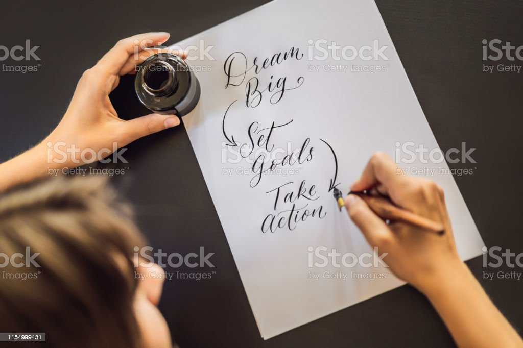 dream big set goals take action. Calligrapher Young Woman writes...