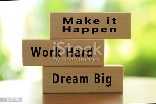Positive inspirational motivational words on wooden blocks - Dream big. Work hard, Make it happen. On blur green bright background. Business and successful concept.