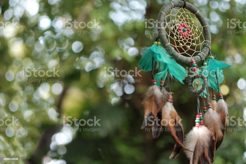 Dream catcher blue coral and natural bokeh background selective focus and blurry. (Vintage style)  boho chic, ethnic amulet. stock photo