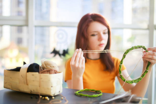 Dream catcher creation in art studio. Young woman making decoration accessory for bedroom. Workshop, hobby, handicraft, creativity concept stock photo