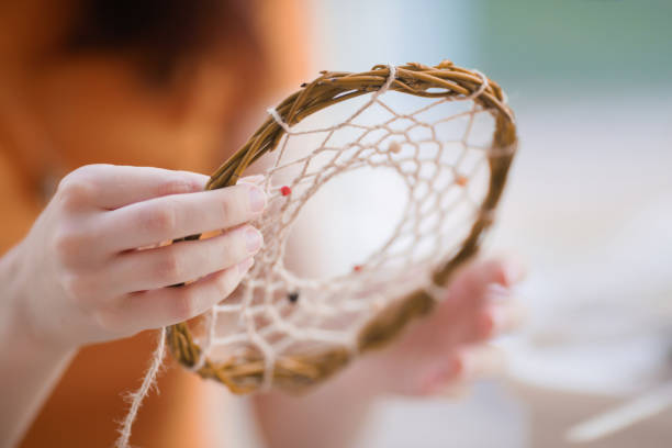 Dream catcher creation in art studio. Young woman making decoration accessory for bedroom, closeup photo. Workshop, hobby, handicraft, creativity concept stock photo