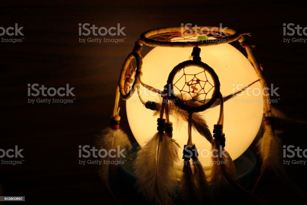 Dream catcher in the dark on light bulb stock photo