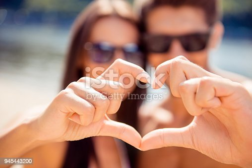 950598260 istock photo dream come true. Happy family on honeymoon gesturing heart with fingers, focus on hands 945443200