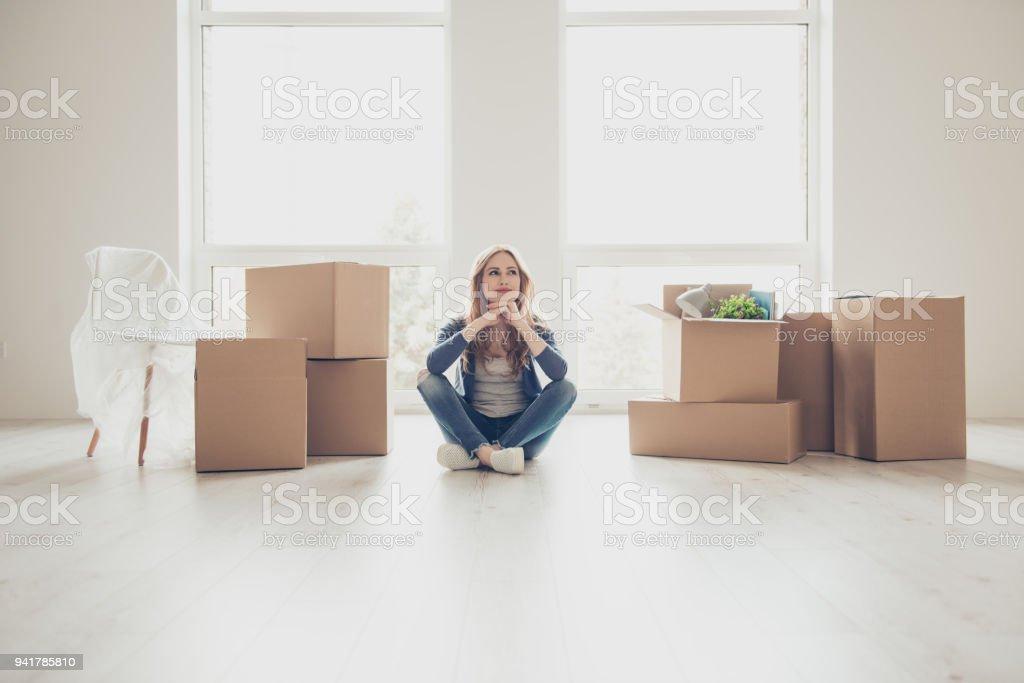 ¡Sueño hecho realidad! Retrato de joven mujer bonita sentada en el suelo y pensando cómo desempaquetar todas las cosas - foto de stock
