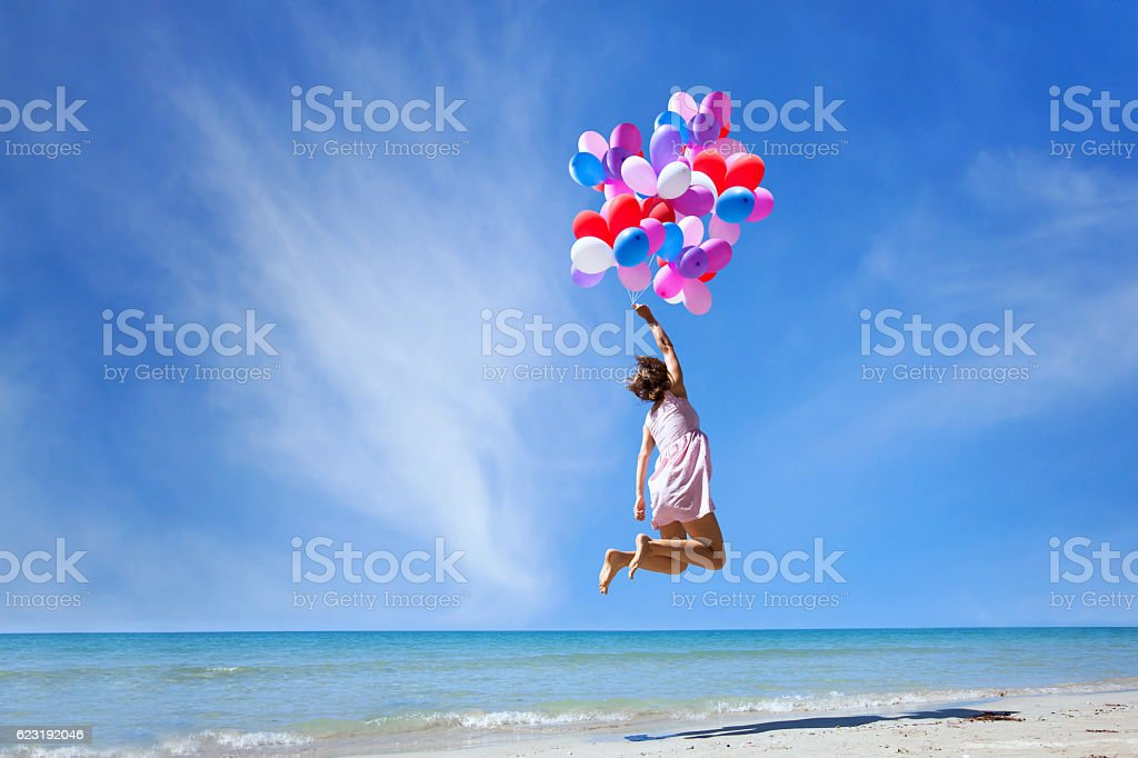 dream concept, girl flying with multicolored balloons, jump - Photo