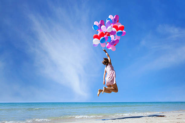 dream concept, girl flying with multicolored balloons, jump - lightweight stock photos and pictures