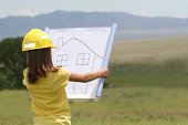 Cute little girl planning her dream house in an open majestic area.