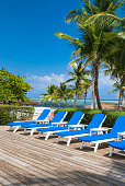 View of deck chairs and palm trees by the stunning waters of the Cayman islands