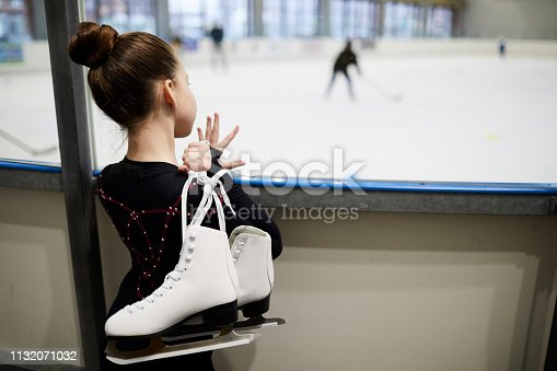 Back view portrait of future figure skater standing by ice rink and watching training, copy space