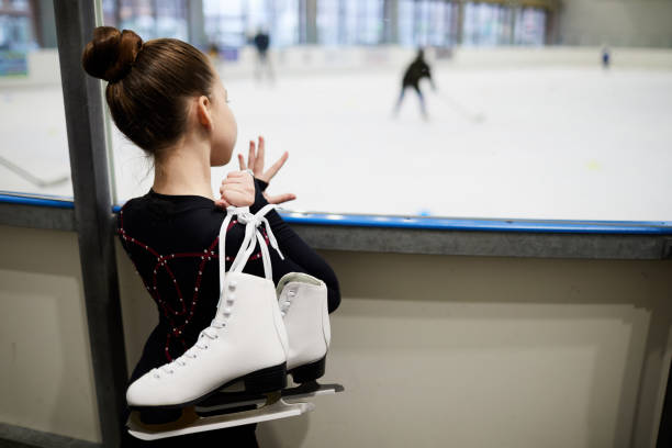 Dream of Figure Skating Back view portrait of future figure skater standing by ice rink and watching training, copy space ice rink stock pictures, royalty-free photos & images