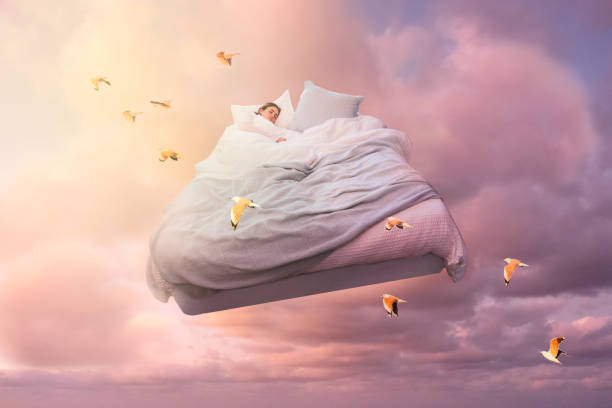 Dream A sleeping girl floats on a bed in the sky and dreamlike stock pictures, royalty-free photos & images