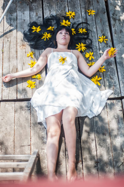 Dream. The young dark-haired girl in the flowers. Raised above the ground, it levitates. Fairy tale. Dreams, flowers, butterfly. stock photo