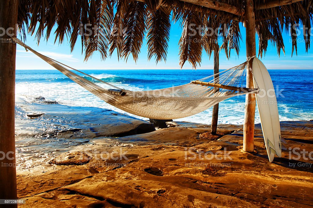 Férias dos seus sonhos na praia com uma rede e prancha, - foto de acervo