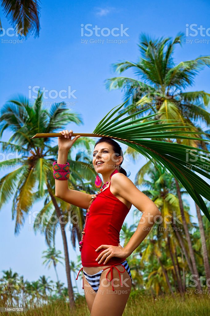 Dream vacation Smiling woman on tropical vacation holding palm leaf above her head, looking in the distance. Coconut palm trees in the background. 30-34 Years Stock Photo