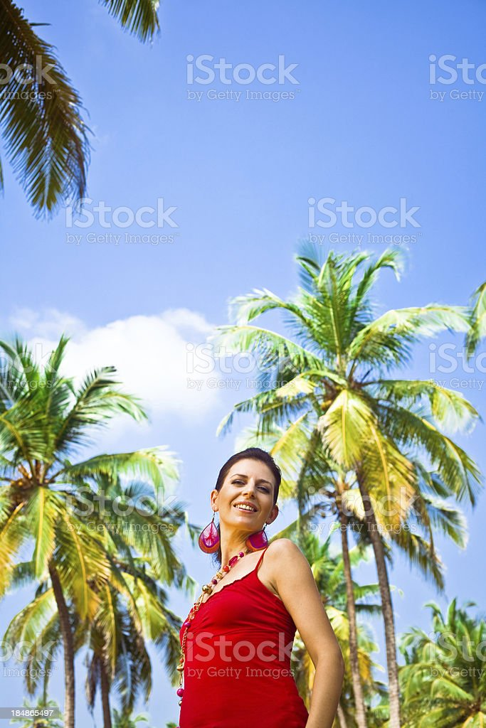 Dream vacation Happy woman on tropical vacation standing against coconut palm trees, smiling at camera. 30-34 Years Stock Photo