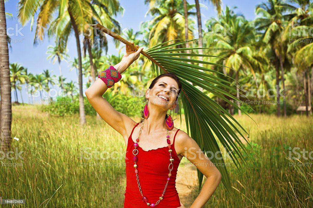 Dream vacation Smiling woman on tropical vacation holding palm leaf above her head. Coconut palm trees in the background. 30-34 Years Stock Photo