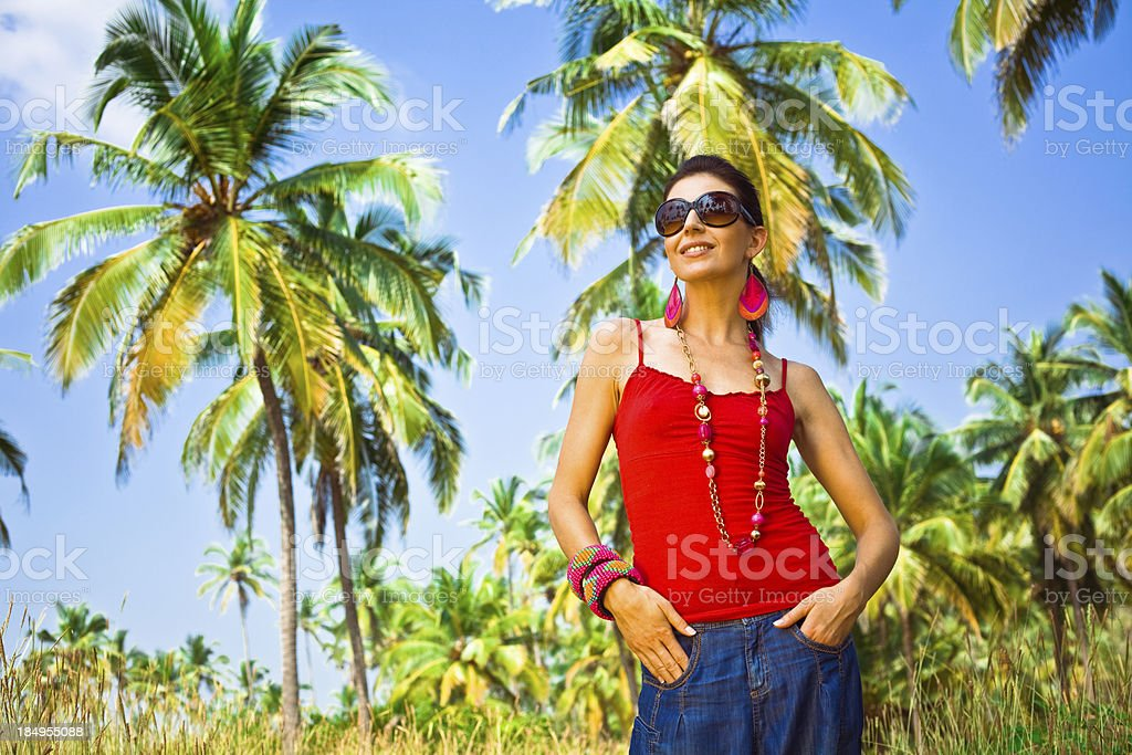 Dream vacation Smiling woman on tropical vacation, looking in the distance. Coconut palm trees and blue sky in the background. 30-34 Years Stock Photo