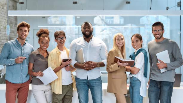 traumarbeit. porträt junger und erfolgreicher mitarbeiter in freizeitkleidung lächelnd vor der kamera, während sie im arbeitsraum stehen - mitarbeiterengagement stock-fotos und bilder