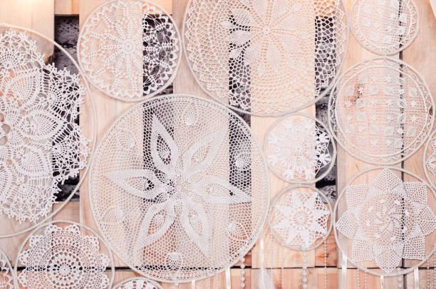 dreamcatcher weiß gestrickt gehäkelt mit weißen federn und perlen hängen an einem hölzernen hintergrund. - traumfänger malerei stock-fotos und bilder
