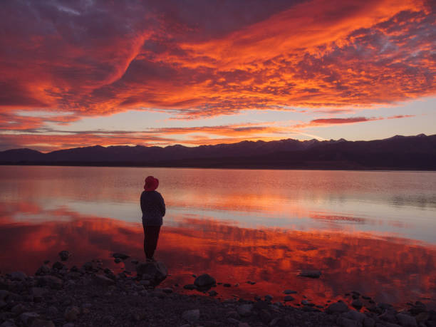 dreamer, silhouette of woman standing along the lake at sunset, human strength, psychology concept stock photo