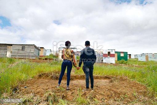 An African heterosexual couple standing on a clean plot of land in a new development of a township above Kayamandi Stellenbosch Cape Town South Africa