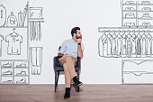 Young handsome man keeping hand on chin and looking away while sitting in the chair against illustration of closet in the background