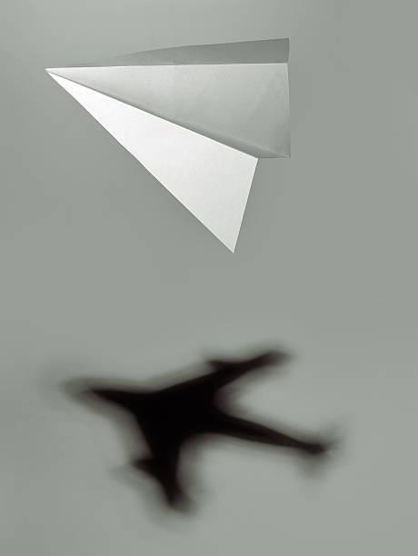 träumen sie groß: papier flugzeug casting eine unglaubliche jet-flugzeug jet - origami mobil stock-fotos und bilder